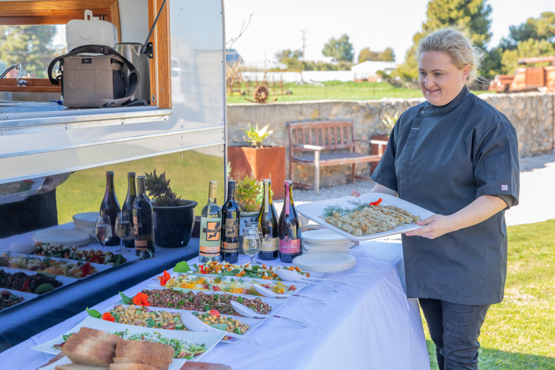 Caroline with serval food dishes in front of the Food Van.