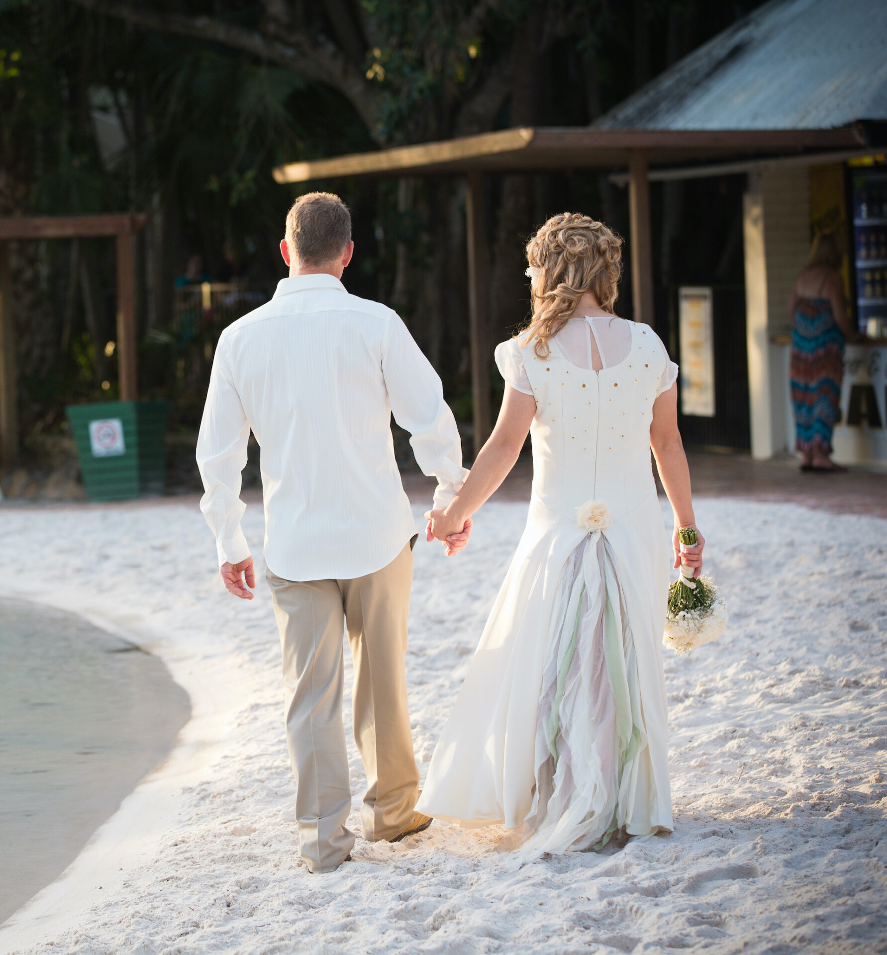 The bride and groom holding hands viewed from behind