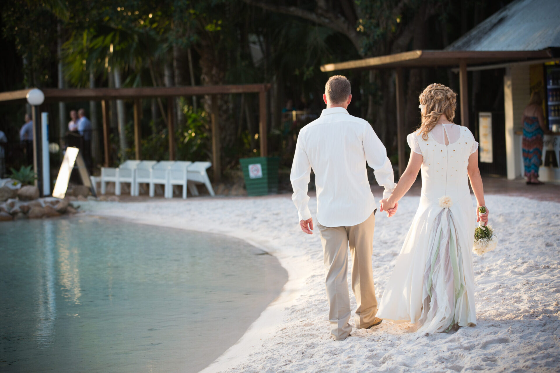 The back of a newly wed couple on the edge of a lagoon.
