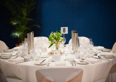 Table with white table cloth set out for a wedding meal.